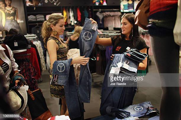 During the grand opening of the HM clothing store newly employed sales representative Jaclyn Ragette helps customer Christina Katker pick out jeans...