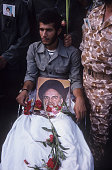During the IranIraq War a disabled veteran of the Iranian Revolutionary Guard Corps holds a picture of Ayatollah Khomeni on Pasdaran's Day...