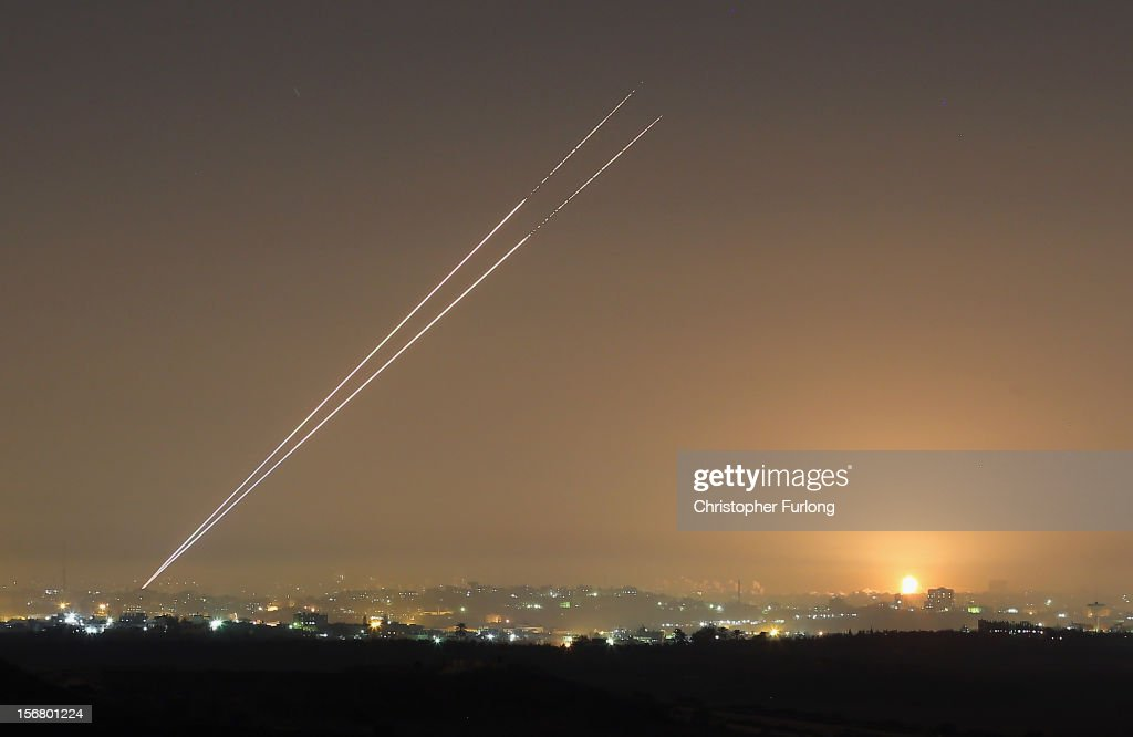 During the last hour of hostilities militants launch rockets from Gaza City as an Israeli bomb explodes on the horizon on November 21 2012 on...