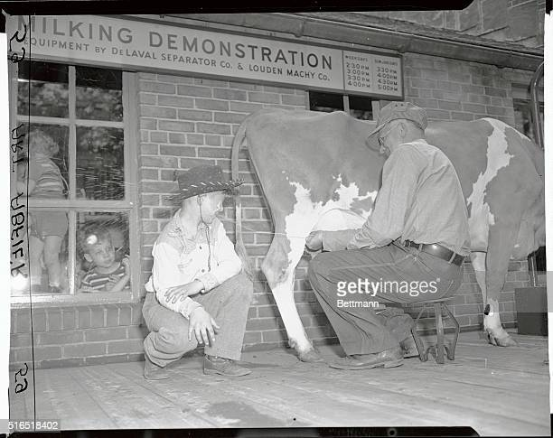 During the milking demonstration at the Bronx Park Zoo farmer Nelson Miller squirts milk into the face of 8 year old Lee Johnson of Belmar New Jersey...
