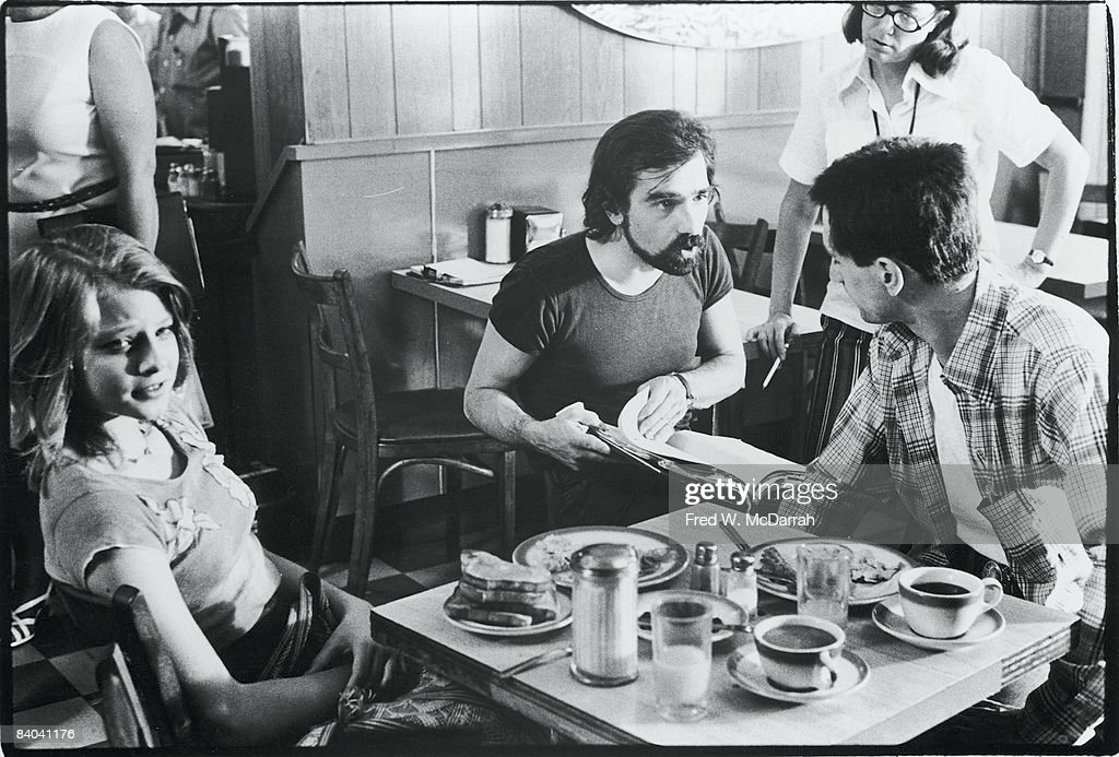 During the production of the film 'Taxi Driver' teenaged American actress Jodie Foster looks at the camera while film director Martin Scorsese...