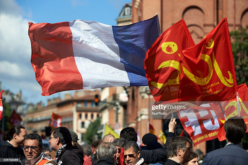 During the traditionnal march for Labor Day on May 1st, a protester hold a French flag amid flags of the 'Young communists' movement. Toulouse. France. May 1st 2016.