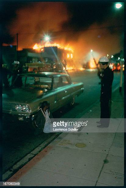 During the Watts Riots while flames burn in the background a police officer stands guard over a handcuffed man on the street and propped against the...