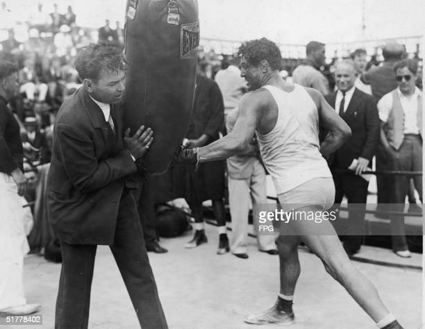 During training for his upcoming heavyweitght title bout American boxer Max Baer works out with a punching bag held by former heavyweight champion...