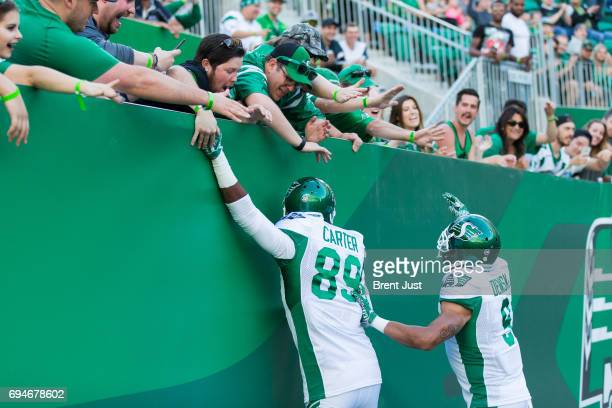 Duron Carter and Nic Demski of the Saskatchewan Roughriders celebrate with fans after a touchdown in the preseason game between the Winnipeg Blue...