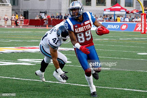 Duron Carter of the Montreal Alouettes runs with the ball past Shea Emry of the Toronto Argonauts during the CFL game at Percival Molson Stadium on...