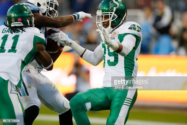 Duron Carter of the Saskatchewan Roughriders comes in to help Ed Gainey of the Saskatchewan Roughriders on stopping SJ Green of the Toronto Argonauts...