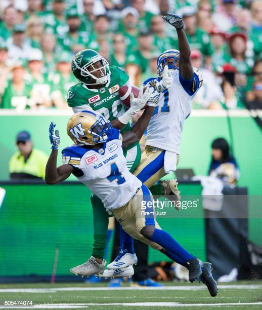 Duron Carter of the Saskatchewan Roughriders makes a catch in tight coverage between Roc Carmichael and Brandon Alexander of the Winnipeg Blue...