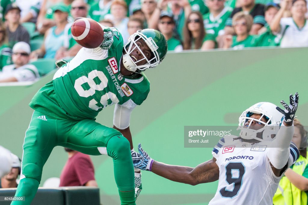 Duron Carter #89 of the Saskatchewan Roughriders makes a great one handed catch over Akwasi Owusu-Ansah #9 of the Toronto Argonauts for a late first half touchdown in the game between the Toronto Argonauts and Saskatchewan Roughriders at Mosaic Stadium on July 29, 2017 in Regina, Canada.