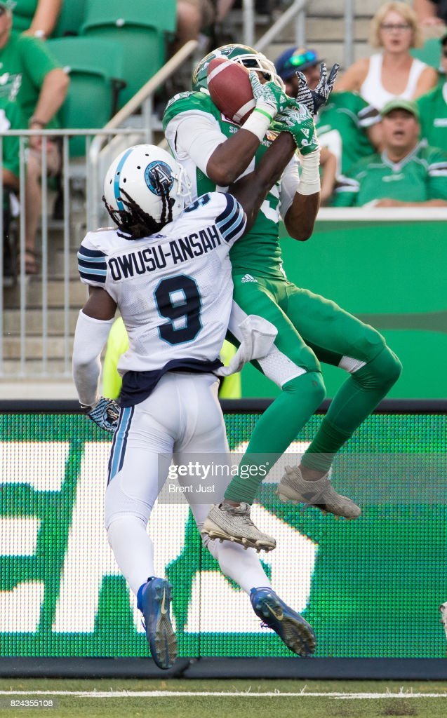 Duron Carter #89 of the Saskatchewan Roughriders makes a leaping catch over Akwasi Owusu-Ansah #9 of the Toronto Argonauts in the second half of the game between the Toronto Argonauts and Saskatchewan Roughriders at Mosaic Stadium on July 29, 2017 in Regina, Canada.