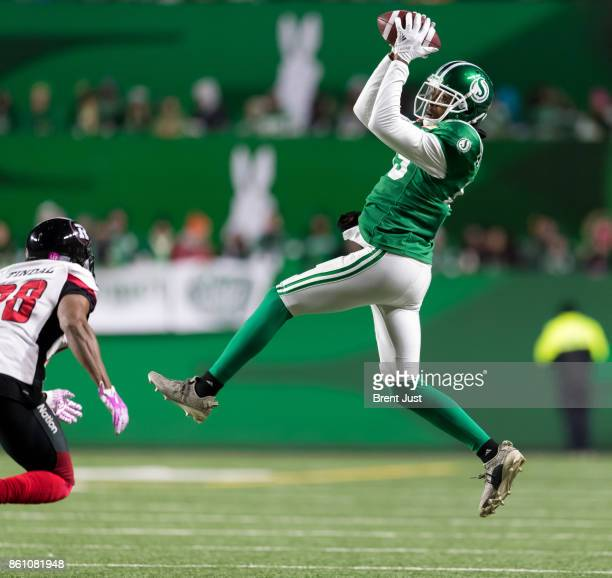 Duron Carter of the Saskatchewan Roughriders takes a peek at Corey Tindal of the Ottawa Redblacks while making a catch in the first half of the game...
