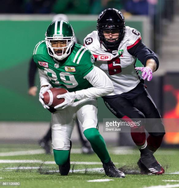 Duron Carter of the Saskatchewan Roughriders tries to run away from Antoine Pruneau of the Ottawa Redblacks after making a catch in the game between...