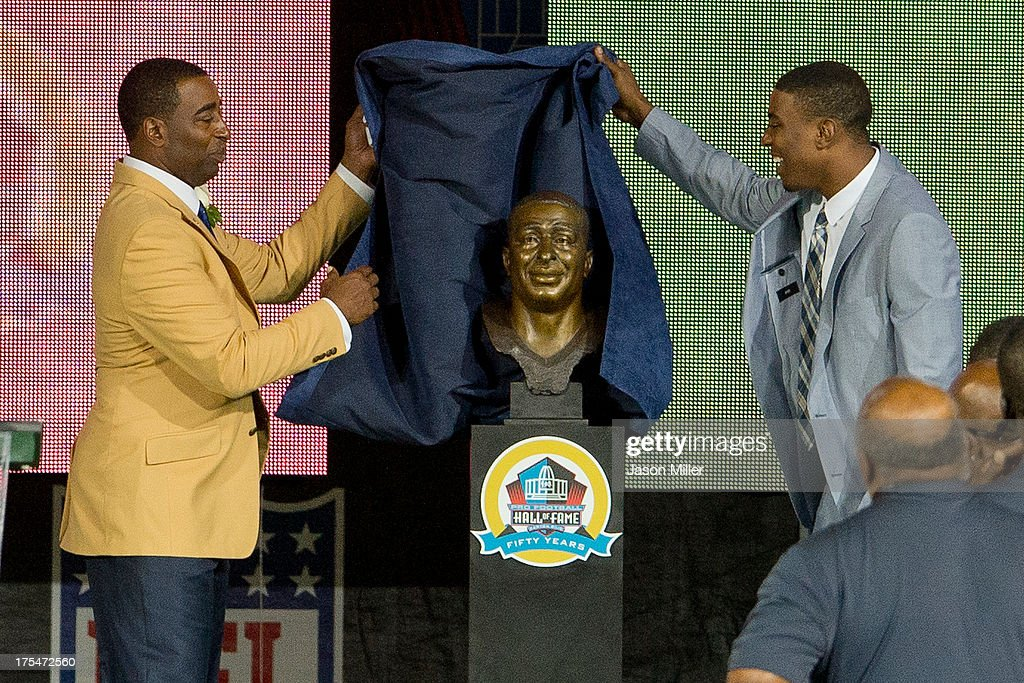 Duron Carter (R) presents his father and former receiver Cris Carter of the Minnesota Vikings with his Hall of Fame bust during the NFL Class of 2013 Enshrinement Ceremony at Fawcett Stadium on Aug. 3, 2013 in Canton, Ohio.