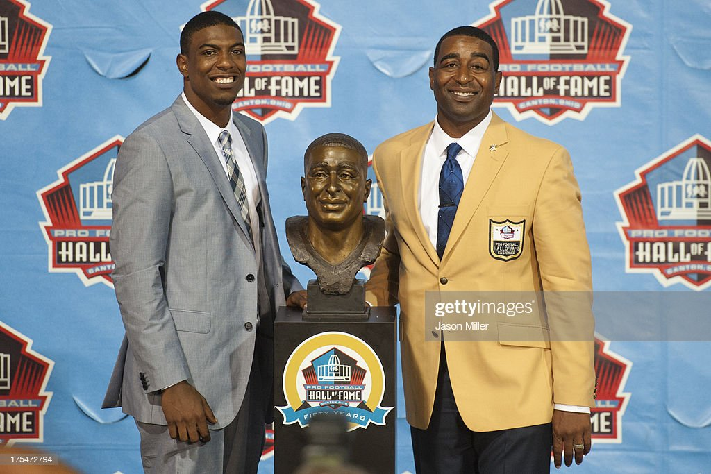 Duron Carter (L) presents his father and former receiver Cris Carter of the Minnesota Vikings with his Hall of Fame bust during the NFL Class of 2013 Enshrinement Ceremony at Fawcett Stadium on Aug. 3, 2013 in Canton, Ohio.
