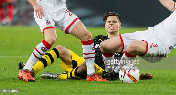 Dusan Svento and Dominique Heintz of Kln challenge Julian Weigl of Borussia Dortmund during the Bundesliga match between 1 FC Koeln and Borussia...