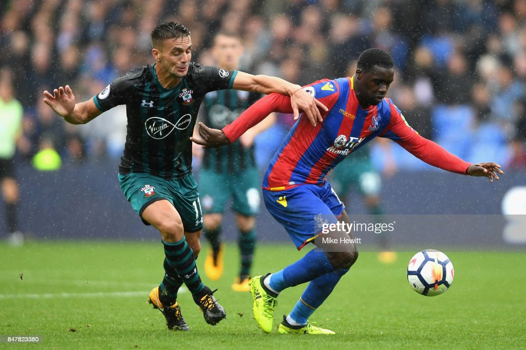 Dusan Tadic of Southampton and Jeffrey Schlupp of Crystal Palace battle for possession during the Premier League match between Crystal Palace and Southampton at Selhurst Park on September 16, 2017 in London, England.