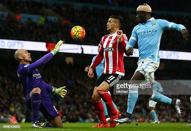 Dusan Tadic of Southampton and Wilfredo Caballero of Manchester City compete for the ball during the Barclays Premier League match between Manchester...