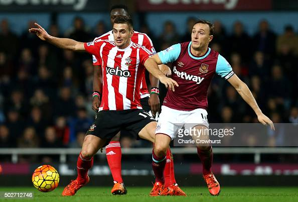 Dusan Tadic of Southampton battles for the ball with Mark Noble of West Ham United during the Barclays Premier League match between West Ham United...