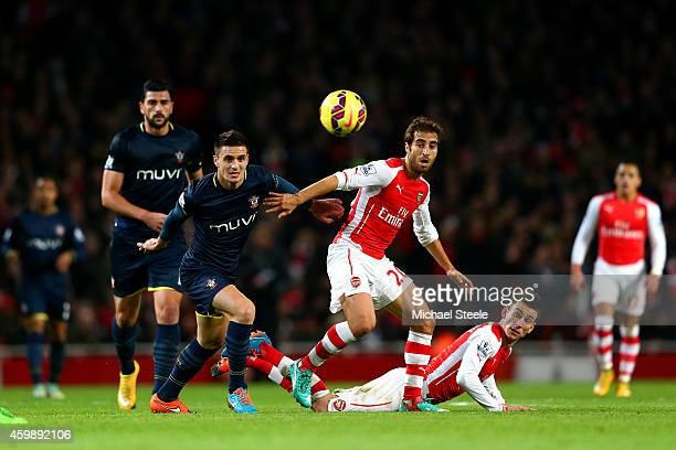 Dusan Tadic of Southampton battles for the ball with Mathieu Flamini and Laurent Koscielny of Arsenal during the Barclays Premier League match...