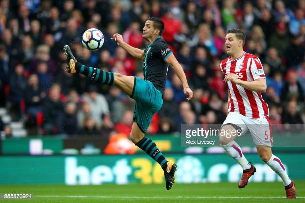 Dusan Tadic of Southampton controls the ball while under pressure from Kevin Wimmer of Stoke City during the Premier League match between Stoke City...