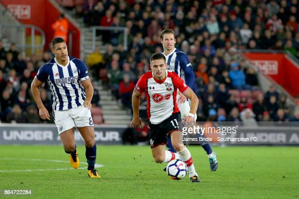 Dusan Tadic of Southampton FC runs the ball past Jake Livermore and Grezegorz Krychowiak of West Bromwhich Albion during the Premier League match...