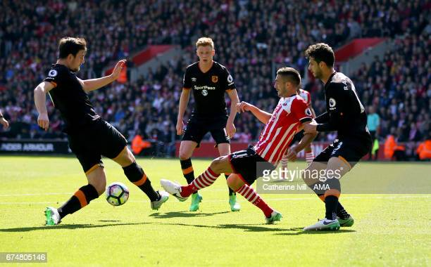 Dusan Tadic of Southampton gets is tackled by Harry Maguire Sam Clucas and Andrea Ranocchia of Hull City during the Premier League match between...