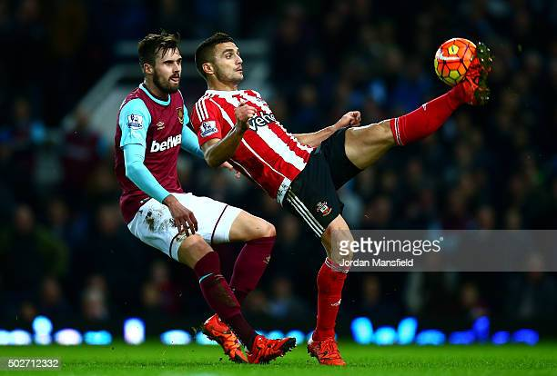 Dusan Tadic of Southampton holds off Carl Jenkinson of West Ham United during the Barclays Premier League match between West Ham United and...