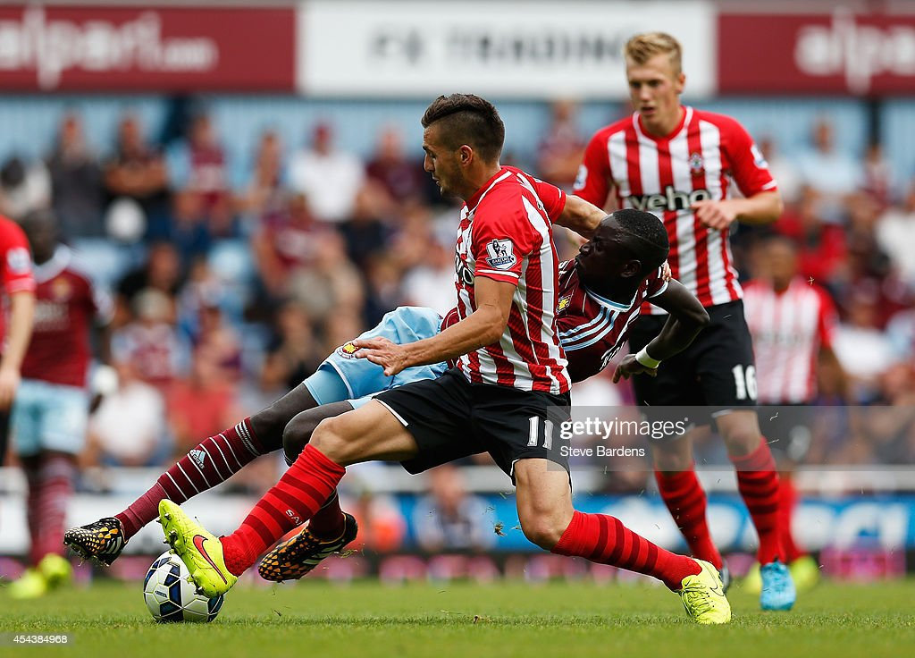 Dusan Tadic of Southampton is tackled by Cheikhou Kouyate of West Ham United during the Barclays Premier League match between West Ham United and Southampton at Boleyn Ground on August 30, 2014 in London, England.