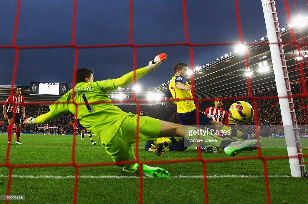 Dusan Tadic of Southampton (R) scores their second goal past Wojciech Szczesny (1) and Mathieu Debuchy of Arsenal (2) during the Barclays Premier League match between Southampton and Arsenal at St Mary's Stadium on January 1, 2015 in Southampton, England.