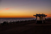 Sunset at Brighton, viewed from the promenade, with a silhouetted foreground