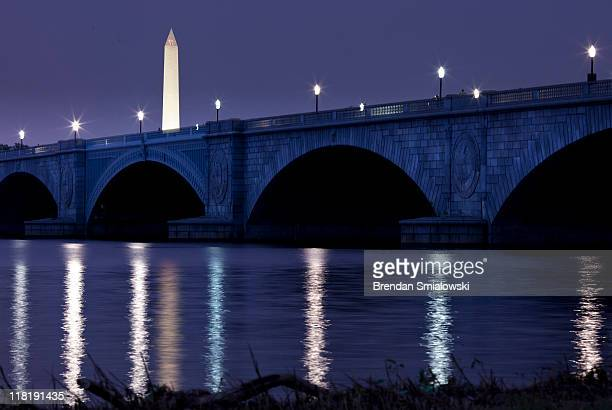 A dusk view of the Washington Monument and Memorial Bridge before a fireworks display in Washington DC from along the shore of the Potomac River July...