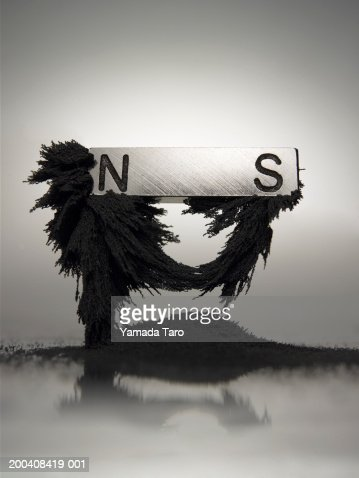 Dust attracted to magnet : Stock Photo