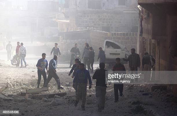 Dust cloud covers streets of Daraa city of Syria and people walk among the debris of houses after Syrian barrel bombs attacks on March 7 2015