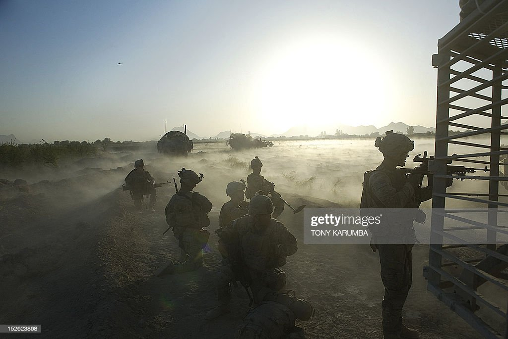 Dust lifts off the ground during an operation at dawn by US Army soldiers attached to the 2nd platoon, C-Coy. 1-23 Infantry based at Zangabad foward operating base in Panjwai ditrict after Anti Personnel Obstacle Breaching System -- abbreviated as A-POBS, [ which are charges fired by rocket and trigger safe detonation of IED's used to make roadside bombs] -- detonate on a nearby road during a dawn operation at Naja-bien village on September 23, 2012. A total of 374 civilians were killed and 581 injured in August as a result of the war in Afghanistan, making it the second deadliest month for civilians since 2007, the United Nations said on September 21. AFP PHOTO/Tony KARUMBA