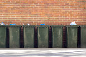 A row of wheelie bins against a brick wall, below a block of apartments in Rhodes.