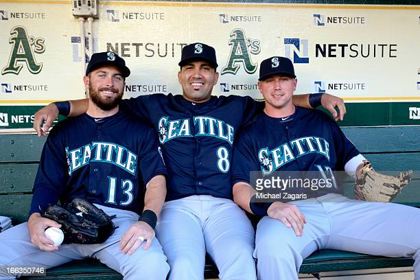 Dustin Ackley Kendrys Morales and Justin Smoak of the Seattle Mariners relax in the dugout prior to the game against the Oakland Athletics at Oco...