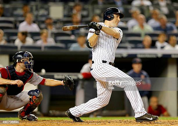 Dustin Ackley of the New York Yankees hits a two run home run in the first inning as Blake Swihart of the Boston Red Sox defends on September 29 2015...