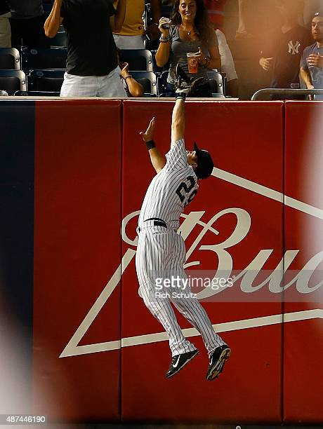 Dustin Ackley of the New York Yankees makes a catch over the wall on a ball hit by Steve Pearce of the Baltimore Orioles in the second inning during...