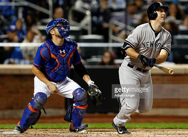 Dustin Ackley of the New York Yankees watches his threerun home run in during the sixth inning in front of Travis d'Arnaud of the New York Mets at...