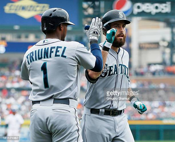 Dustin Ackley of the Seattle Mariners celebrates his three run fifth inning home run with Carlos Triunfel while playing the Detroit Tigers at...