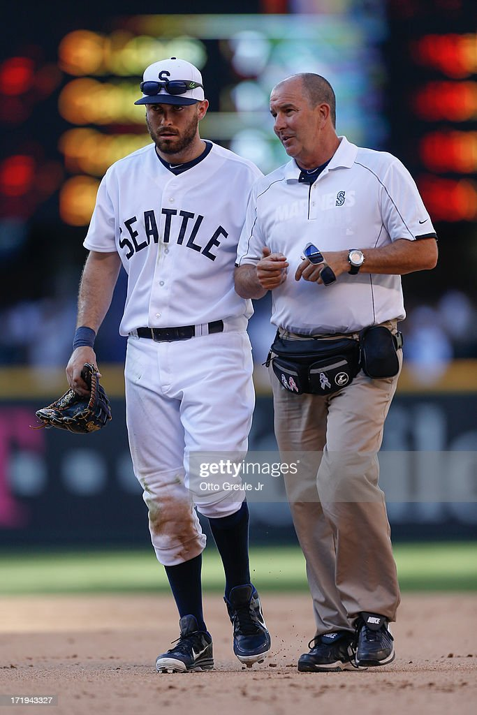 Dustin Ackley #13 of the Seattle Mariners comes out of the game with help from trainer Rick Griffin after diving for a fly ball by Alfonso Soriano of the Chicago Cubs in the ninth inning at Safeco Field on June 29, 2013 in Seattle, Washington.