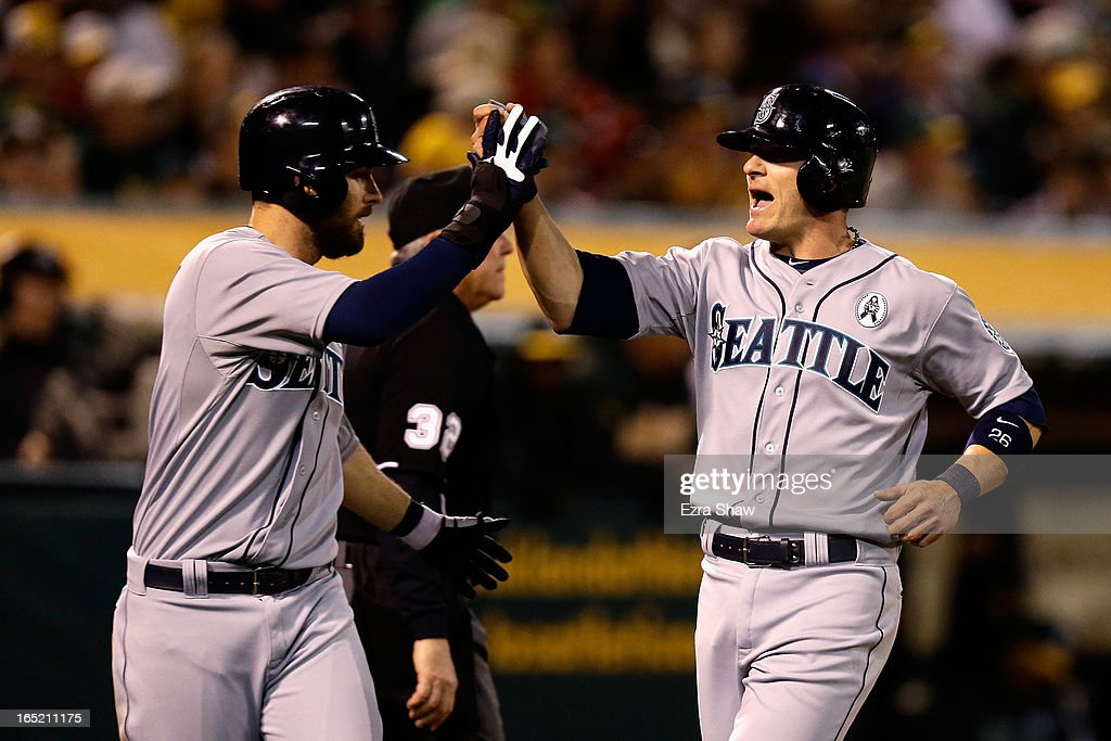 <a gi-track='captionPersonalityLinkClicked' href=/galleries/search?phrase=Dustin+Ackley&family=editorial&specificpeople=4352278 ng-click='$event.stopPropagation()'>Dustin Ackley</a> #13 of the Seattle Mariners congratulates <a gi-track='captionPersonalityLinkClicked' href=/galleries/search?phrase=Brendan+Ryan&family=editorial&specificpeople=835643 ng-click='$event.stopPropagation()'>Brendan Ryan</a> #26 of the Seattle Mariners after they both scored on a single by Franklin Gutierrez #21 in the fifth inning of their game against the Oakland Athletics during Opening Day at O.co Coliseum on April 1, 2013 in Oakland, California.
