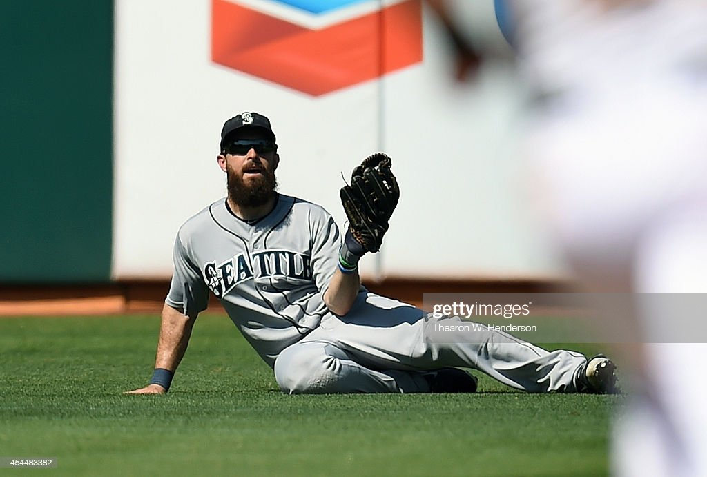 <a gi-track='captionPersonalityLinkClicked' href=/galleries/search?phrase=Dustin+Ackley&family=editorial&specificpeople=4352278 ng-click='$event.stopPropagation()'>Dustin Ackley</a> #13 of the Seattle Mariners goes into a slide to make a catch and take a hit away from Eric Sogard of the Oakland Athletics in the bottom of the seventh inning at O.co Coliseum on September 1, 2014 in Oakland, California. The Athletics won the game 6-1.