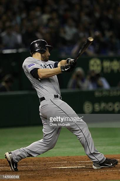 Dustin Ackley of the Seattle Mariners hits a single to get home team mate Brendan Ryan in the 11th inning against the Oakland Athletics during the...