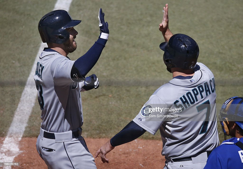 Dustin Ackley #13 of the Seattle Mariners is congratulated by Kelly Shoppach #7 after hitting a grand slam home run in the fourth inning during MLB game action against the Toronto Blue Jays on May 4, 2013 at Rogers Centre in Toronto, Ontario, Canada.