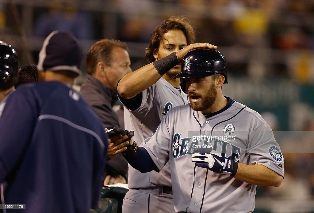 Dustin Ackley #13 of the Seattle Mariners is congratulated by teammates after he scored on a single by Franklin Gutierrez #21 in the fifth inning of their game against the Oakland Athletics during Opening Day at O.co Coliseum on April 1, 2013 in Oakland, California.