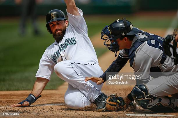 Dustin Ackley of the Seattle Mariners is tagged out by catcher Brian McCann of the New York Yankees attempting to score from second on a single by...
