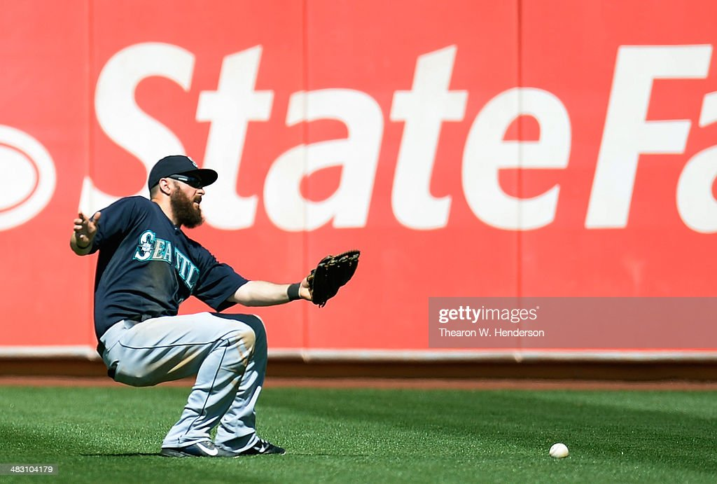 Dustin Ackley #13 of the Seattle Mariners loses this ball in the sun off the bat of John Jason #5 of the Oakland Athletics (not pictured) in the bottom of the second inning at O.co Coliseum on April 6, 2014 in Oakland, California.