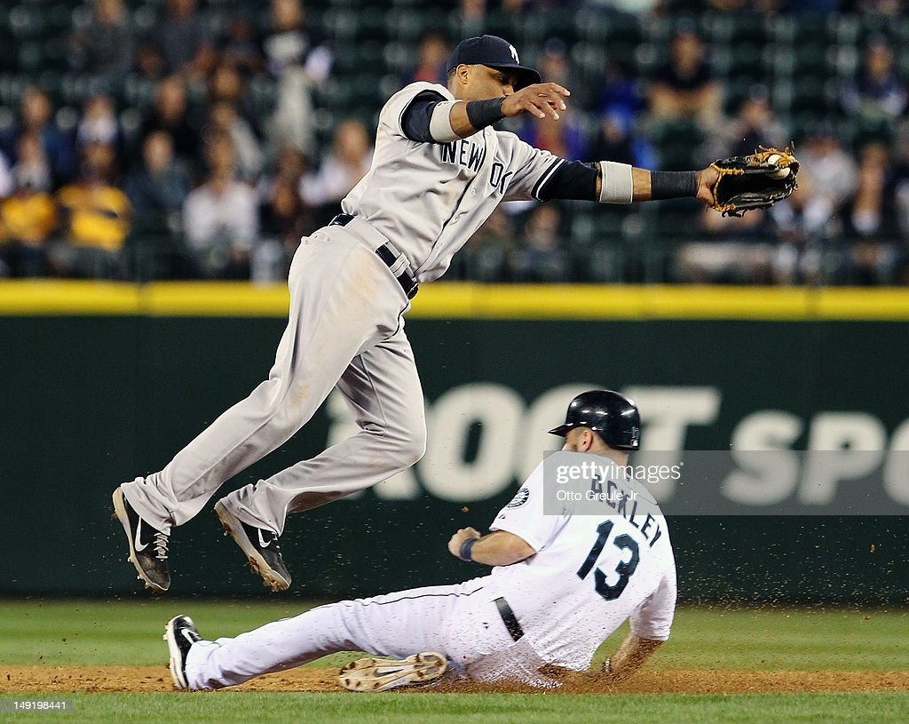 Dustin Ackley #13 of the Seattle Mariners steals second against Robinson Cano #24 of the New York Yankees at Safeco Field on July 24, 2012 in Seattle, Washington.