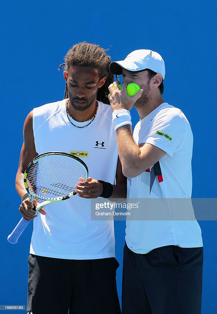Dustin Brown and Christopher Kas of Germany talk tactics in their first round doubles match against Marcel Granollers and Marc Lopez of Spain during...